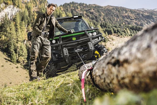 Man pulling a log with a Warn winch attached to his John Deere XUV Series Gator