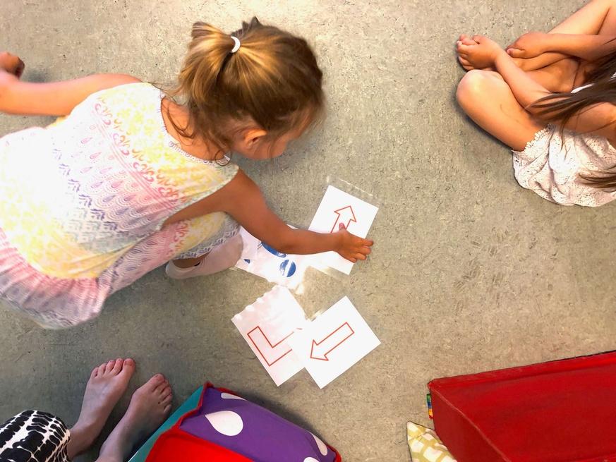 et barn plukker opp et av flere ark med en pil på