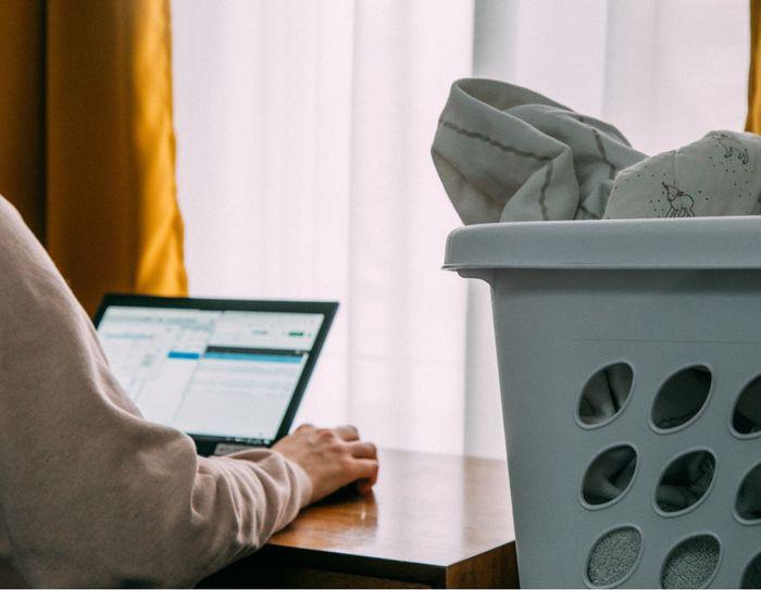 Person sitter konsentrert på hjemmekontor med skittentøyskurv rett ved siden.