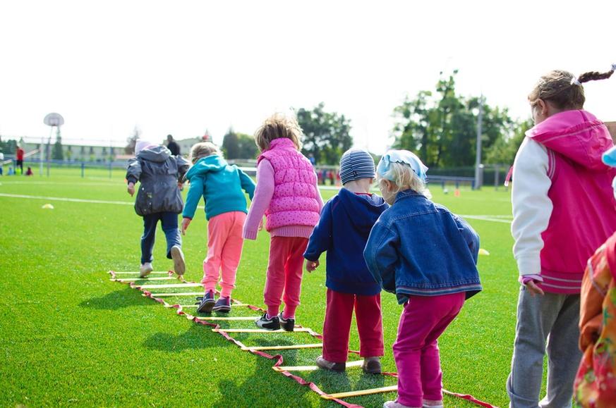 syv barn som aktiviserer seg på en fotballbane: hopper i rutene på en liggende stige
