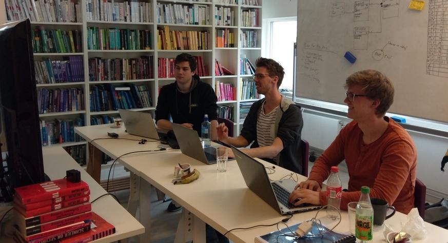 Tre unge menn som mob-programmerer foran en felles skjerm.