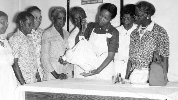 A black nurse showing black midwives how to use a portable scale to weigh babies.