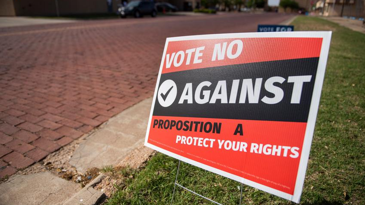 """A red and black sign posted near a sidewalk that reads: """"Vote NO Against Proposition A Protect your Rights"""""""
