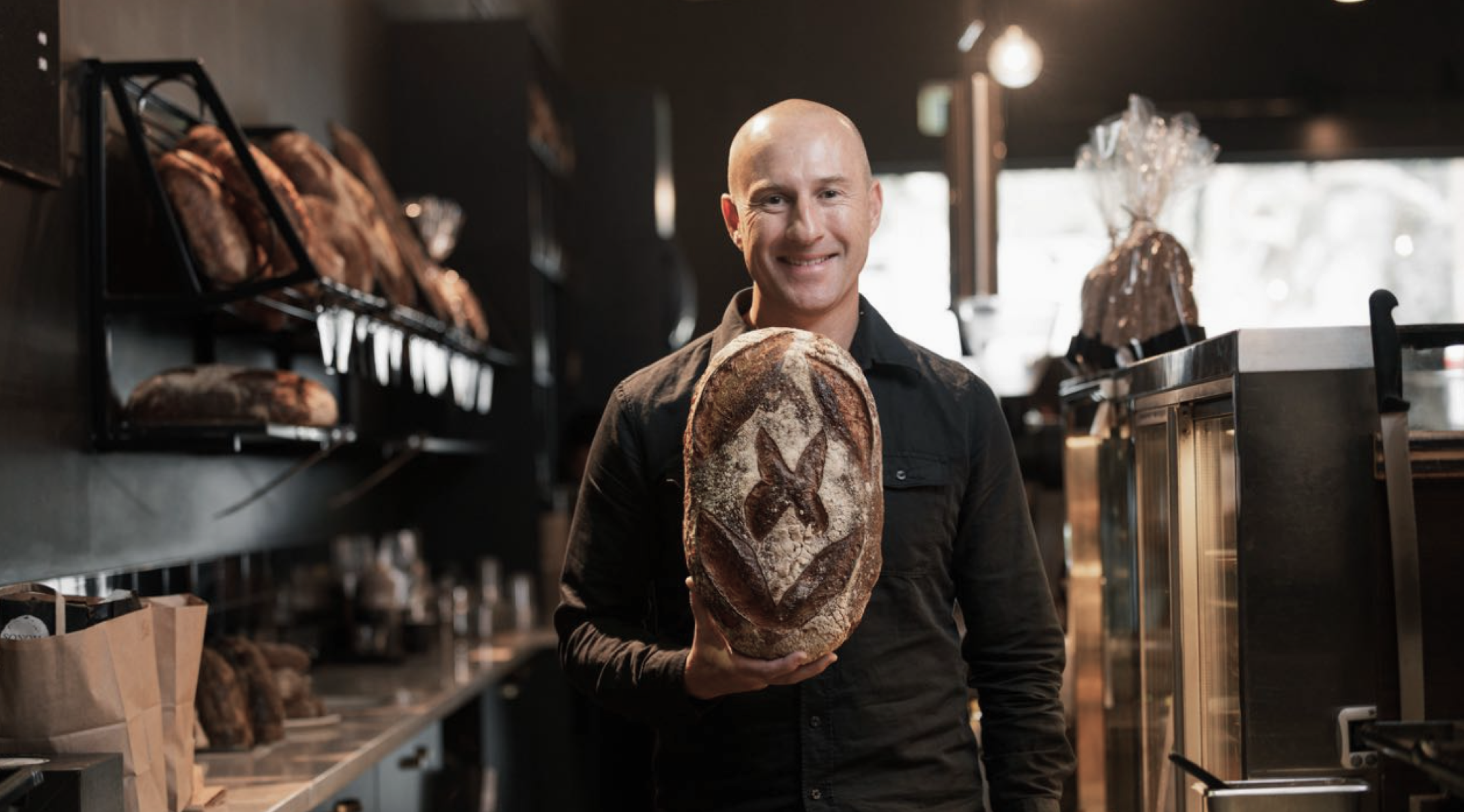 Founder of Sonoma Baking Company holding a loaf of bread