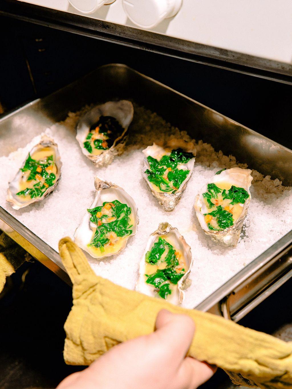 Gratinerte østers med spinal og mezcal-beurre blanc.