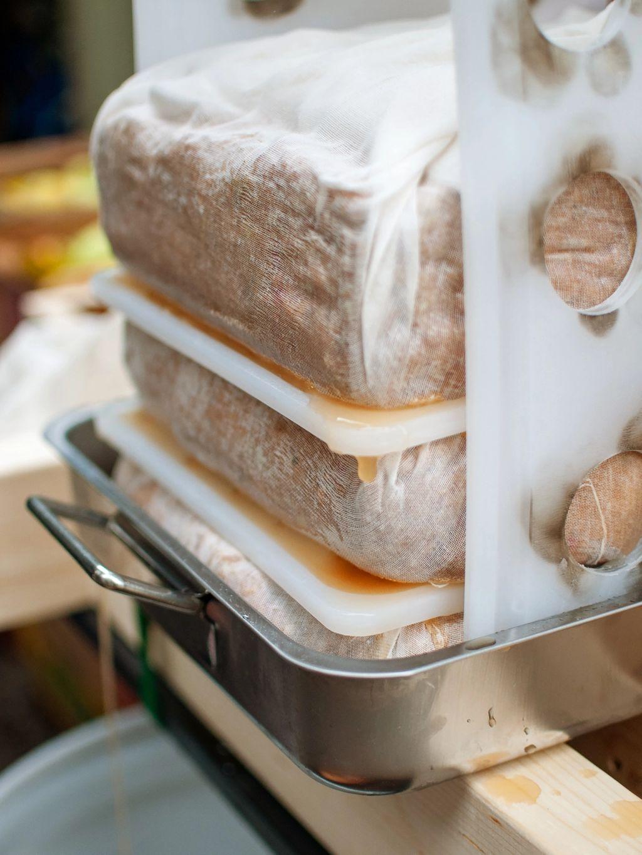Rektangulære pakker av kverna eple presses –med uthullede plastfjøler som mellomlegg. Ut pipler mosten.