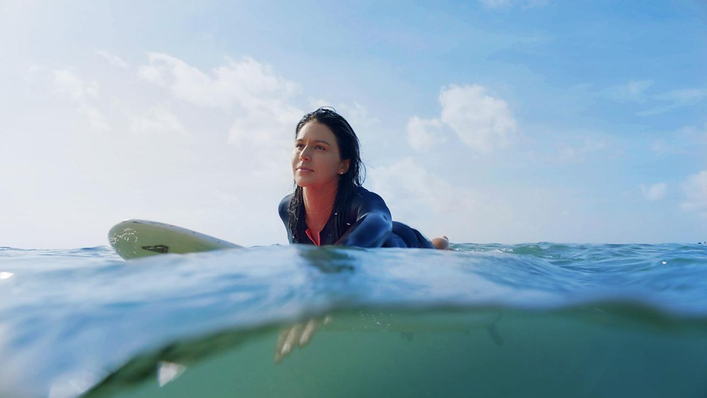 Tulsi Gabbard in the water, surfing.
