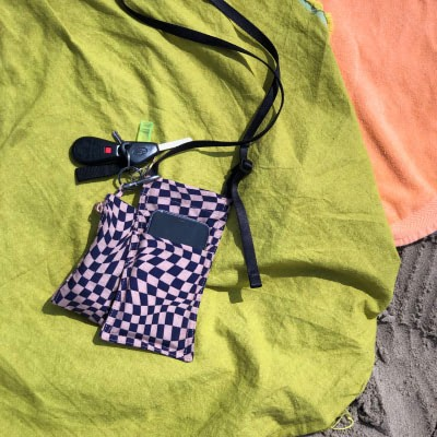 A checkerboard phone pouch laying on a green picnic blanket