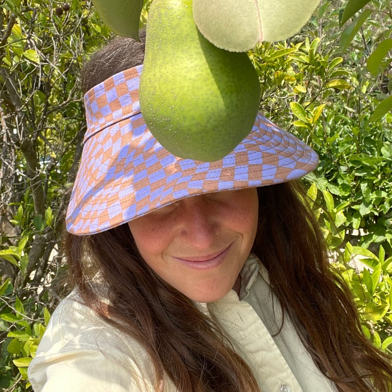 A lavender trippy checker patterned visor on a smiling woman in front of a pear tree
