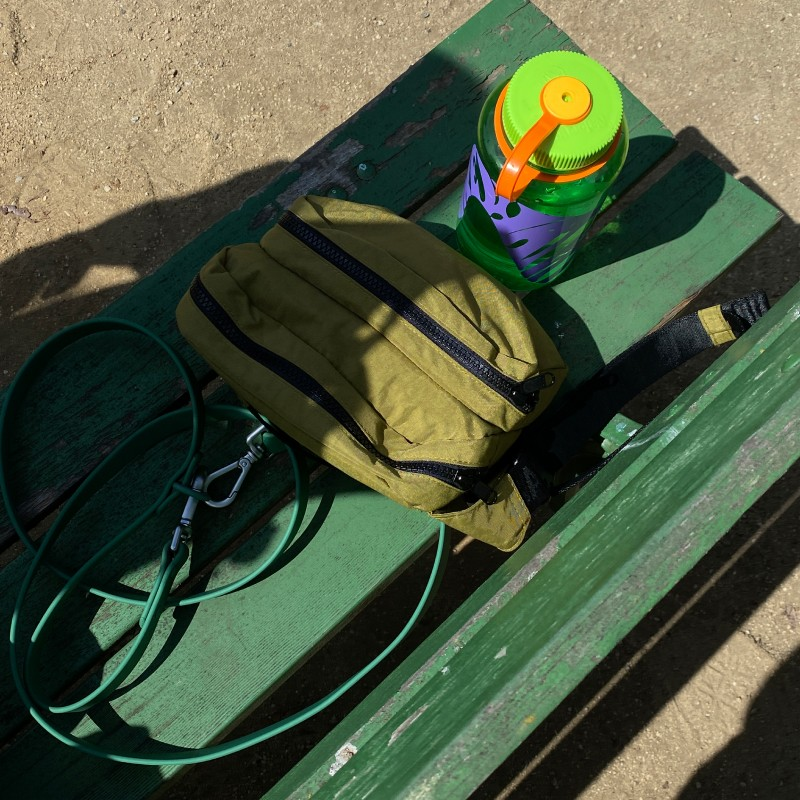 a moss baggu fanny pack and water bottle on a park bench