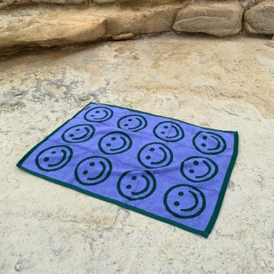 A green and blue happy face towel laying in the sand