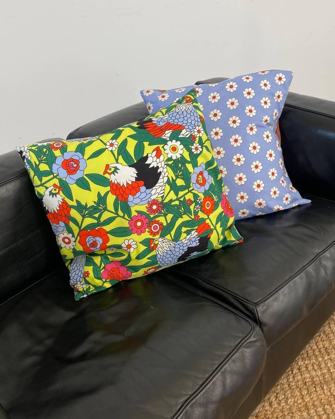 Two throw pillows on a black leather sofa