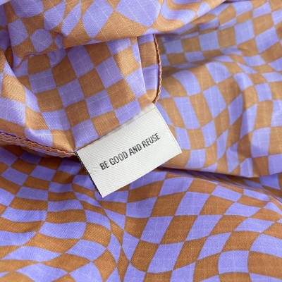 detail of lavender trippy checker ripstop nylon and tag reading be good and reuse