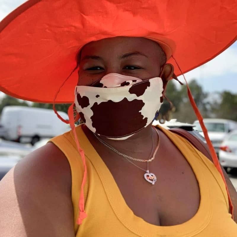 A woman wearing a cowprint mask and a red sun hat