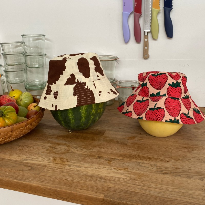 a brown cow bucket hat on a watermelon and a strawberry bucket hat on a melon on a kitchen counter
