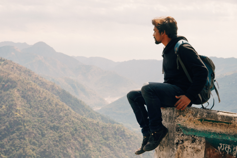 Man sitting on top of mountain overlooking valley