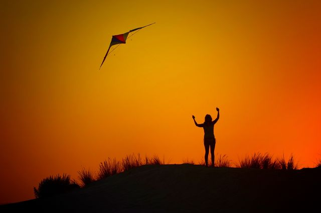Woman in sunset with arms up and kite flying above her