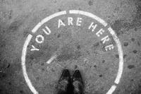 You are here text writing on ground in circle with feet standing in it