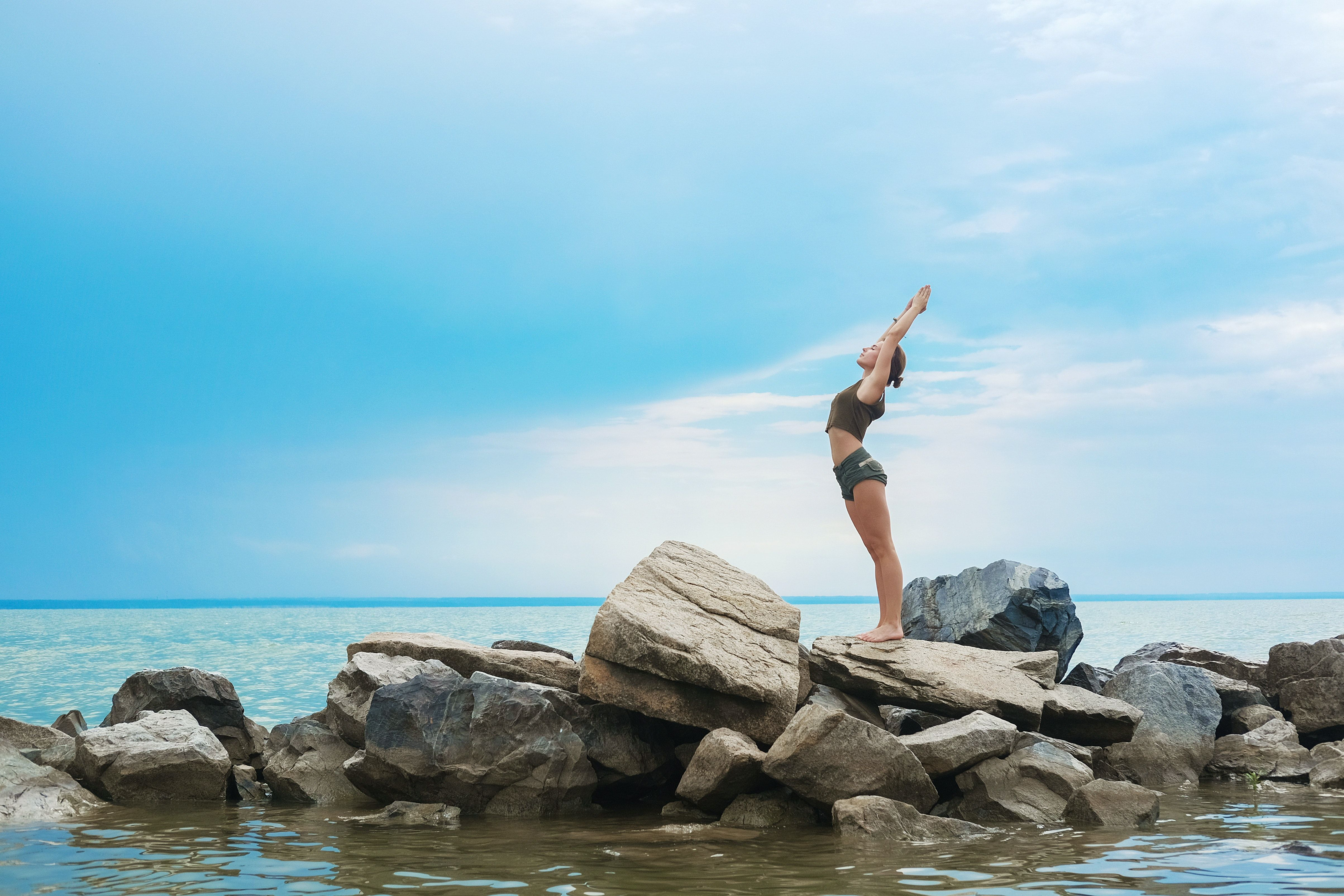 woman on rocks in sea reaching for sky
