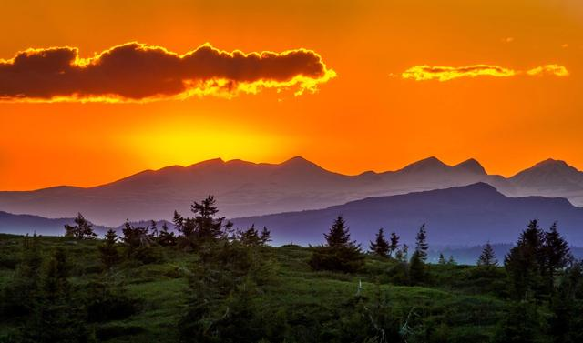Colorful sunrise over ocean and mountains