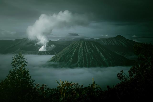 Erupting volcano in lush landscape