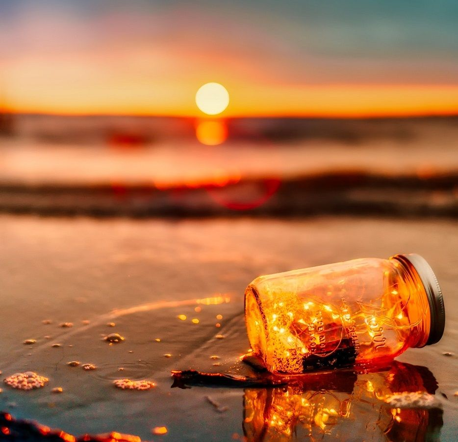 Jar on beach with sunset in background