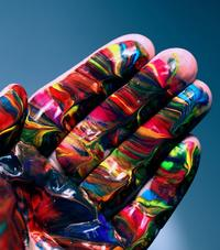 Human hand facing palm with swirled colors painted on it