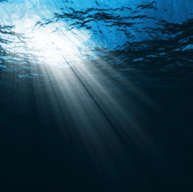 looking up at rays of light coming from sky through water