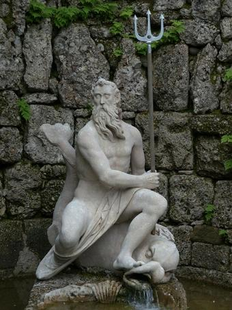 Statue of Neptune with his trident against rocks