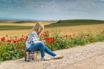 Woman sitting on side of the road with flowers