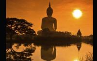 Buddhist statue in distance with sunset