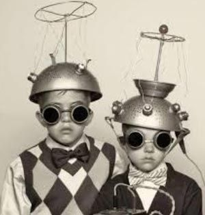 Old picture of kids with metal saucers on heads with antennas