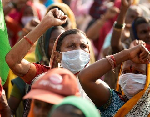 Image of an Indian farmer with facemask and raised fist and the 2021 farmer's protest