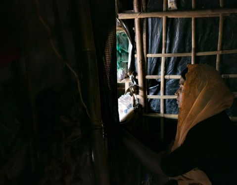 image of Rohingya woman with yellow headscarf looking out a window