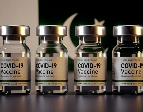 An image of COVID-19 vaccines with the Pakistani flag behind them