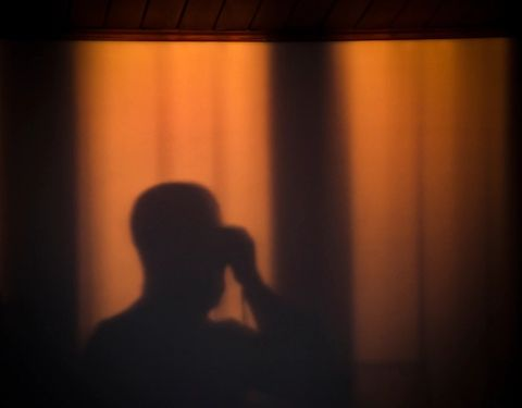Image of a person in the shadows in orange light