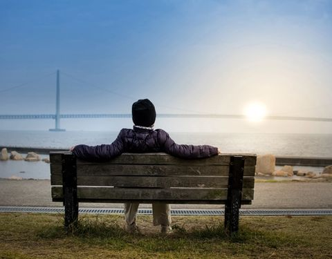 Picture of a person on a bench, resting and looking at the sea