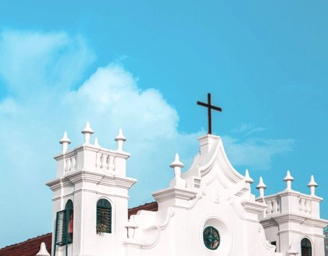 white church with blue shutters and a black cross against blue sky