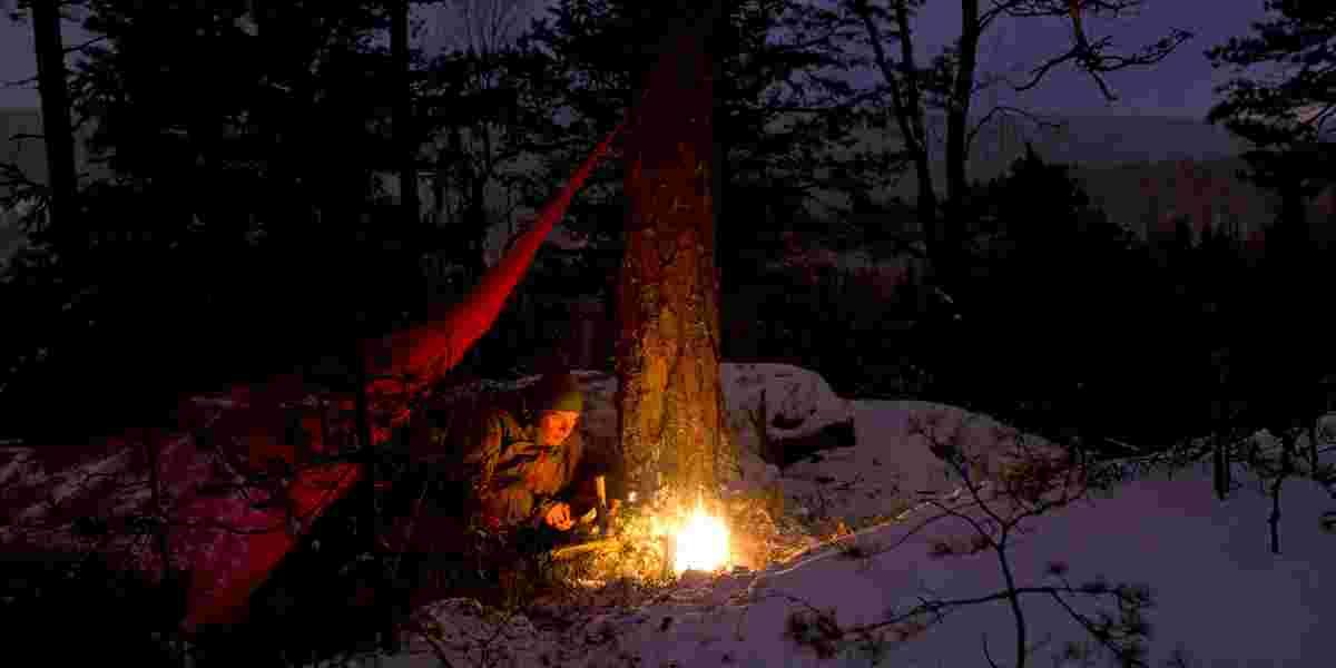 Overnatting ute under tarp (duk, pressening) om vinteren. Vinterkveld.