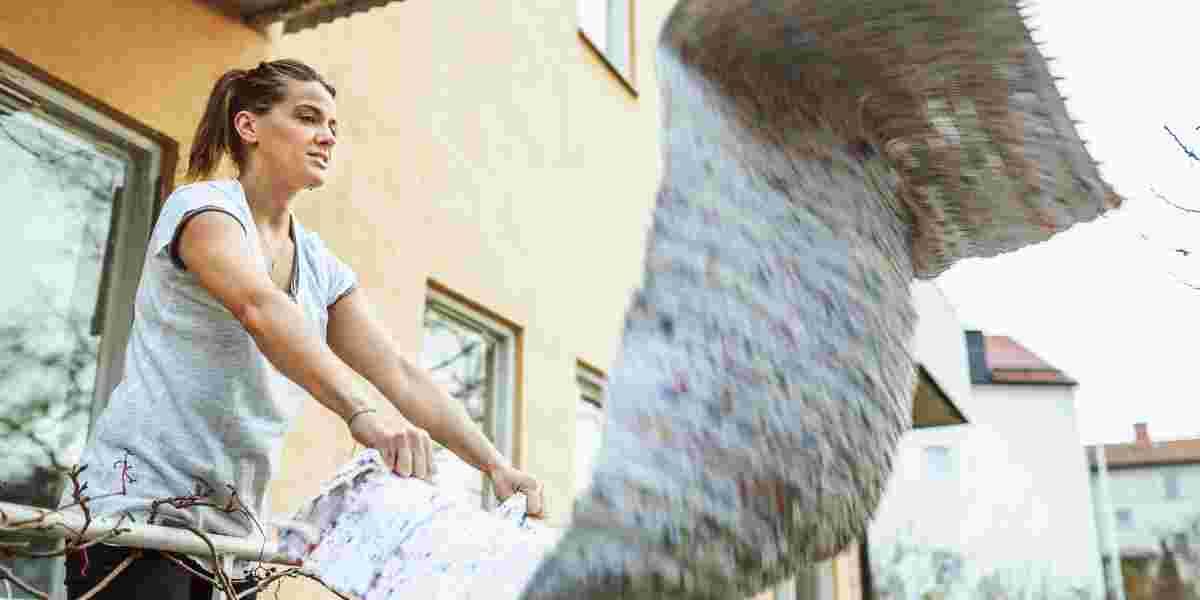 Dame som rister teppe under vårrengjøring