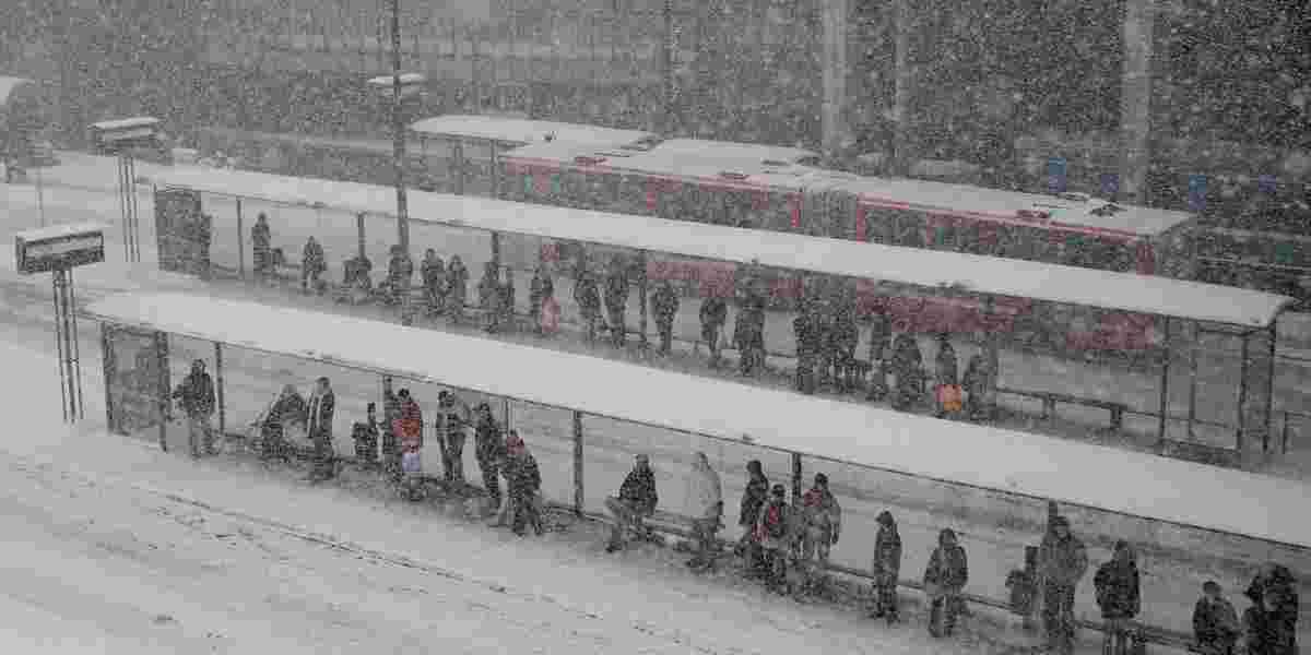 Mennesker som venter på tog i snøstorm