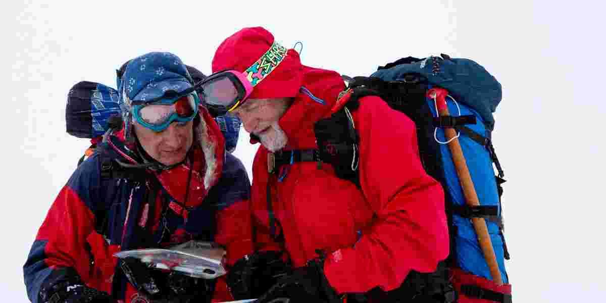 To menn på skitur i fjellet studerer kartet. Kart og kompass.