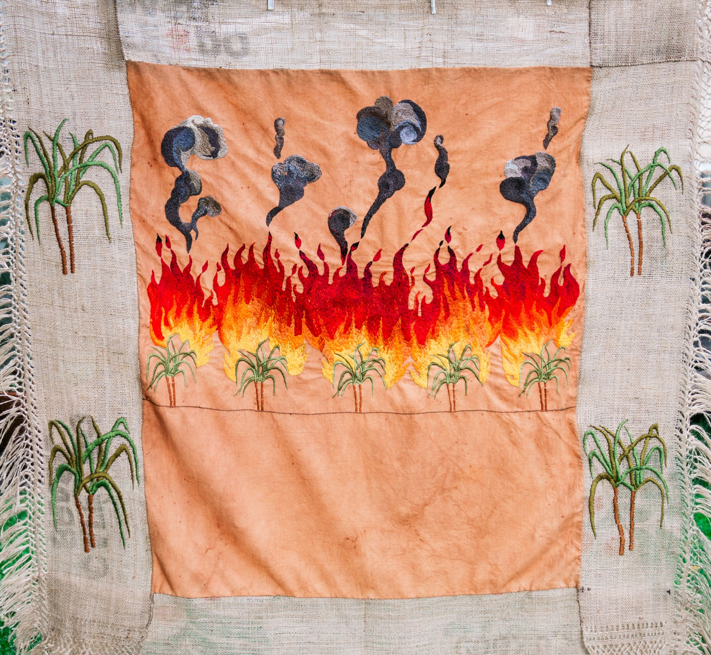 Quishile Charan, Burning Ganna Khet (Burning Sugarcane Farm), 2021, 153cm by 152cm. Technique: hand dyed textile, embroidery thread, cotton, hessian sacks. Textile is naturally dyed with avocado seeds. Image by Matavai Taulangau