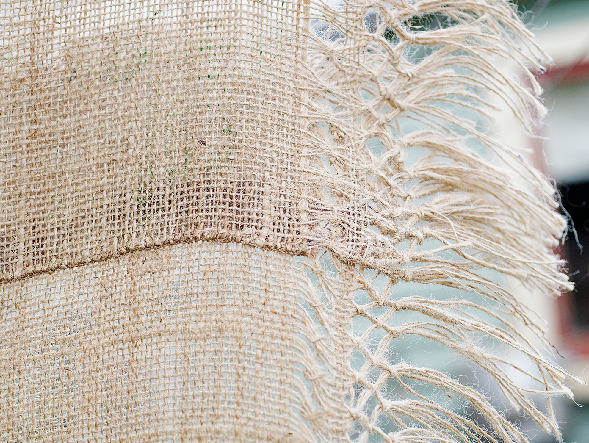 Quishile Charan, Burning Ganna Khet (Burning Sugarcane Farm), 2021, 153cm by 152cm, close up of weaving detail. Technique: hand dyed textile, embroidery thread, cotton, hessian sacks. Textile is naturally dyed with avocado seeds. Image taken by: Raymond Sagapolutele.