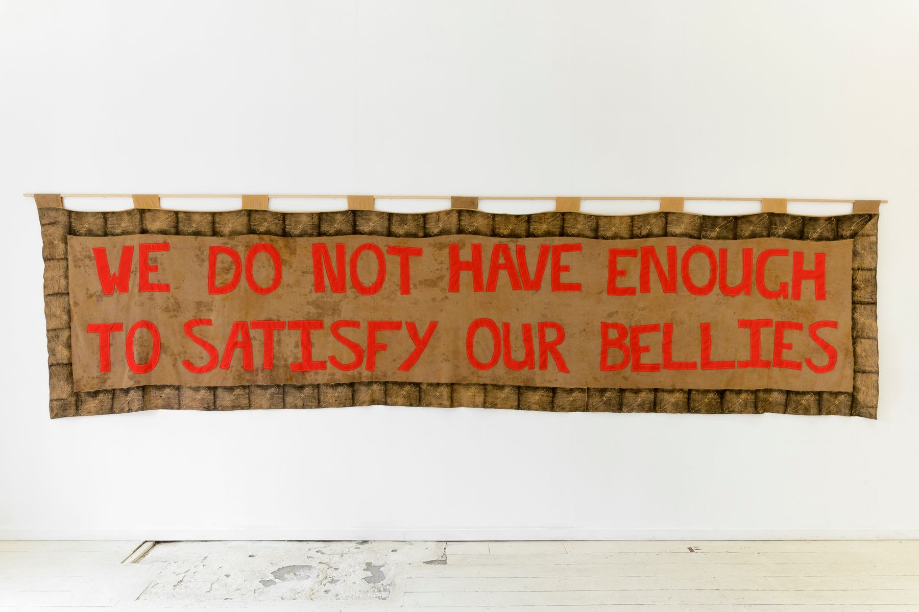 Quishile Charan, We Do Not Have Enough to Satisfy Bellies Protest Banner, 2019, cotton, textile ink, natural dye: aal bark and kumkum seeds, 493 x 117 cm.