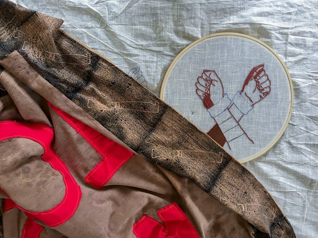 Image of textile-making by Quishile. A brown banner is laid out with red lettering and light beige block prints of machete knives. Embroidery in progress of two hands crossed in embroidery hoop is next to the banner in the upper right corner.