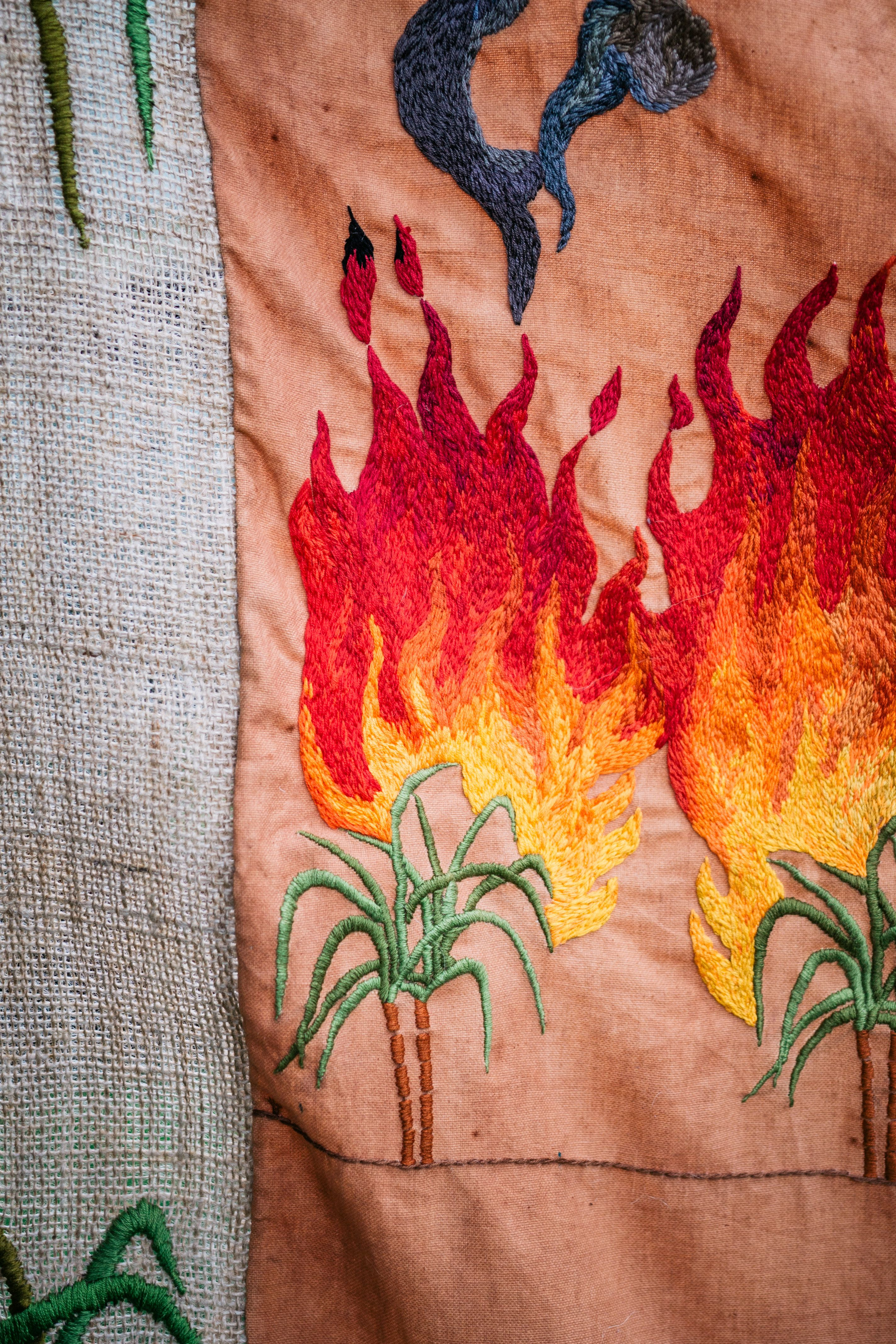Quishile Charan, Burning Ganna Khet, 2021, cotton, embroidery thread, hessian sacks, natural dye: avocados, 153cm by 152cm. Close up of embroidery. Image taken by: Matavai Taulangau.