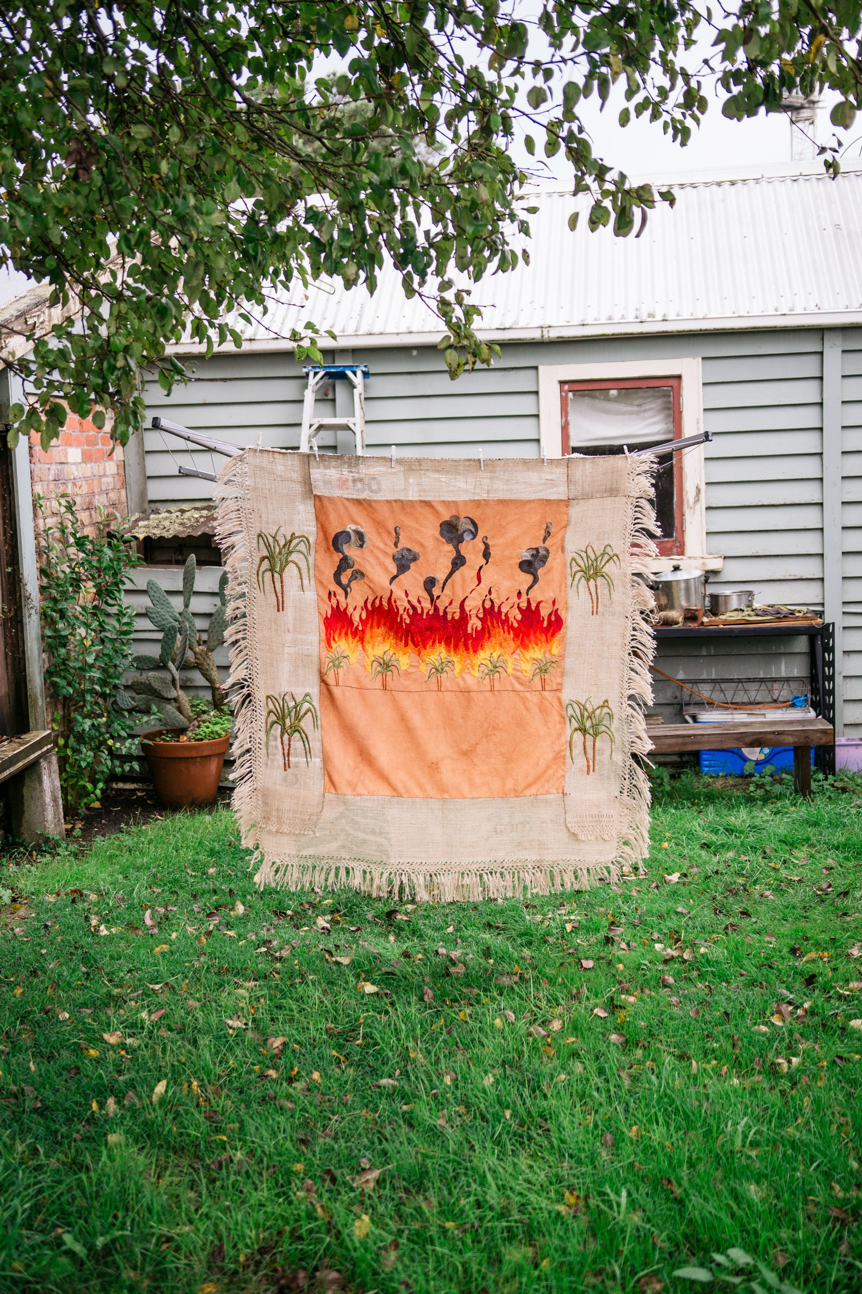 Quishile Charan, Burning Ganna Khet (Burning Sugarcane Farm), 2021, 153cm by 152cm, production still. Technique: hand dyed textile, embroidery thread, cotton, hessian sacks. Textile is naturally dyed with avocado seeds. Image by Matavai Taulangau