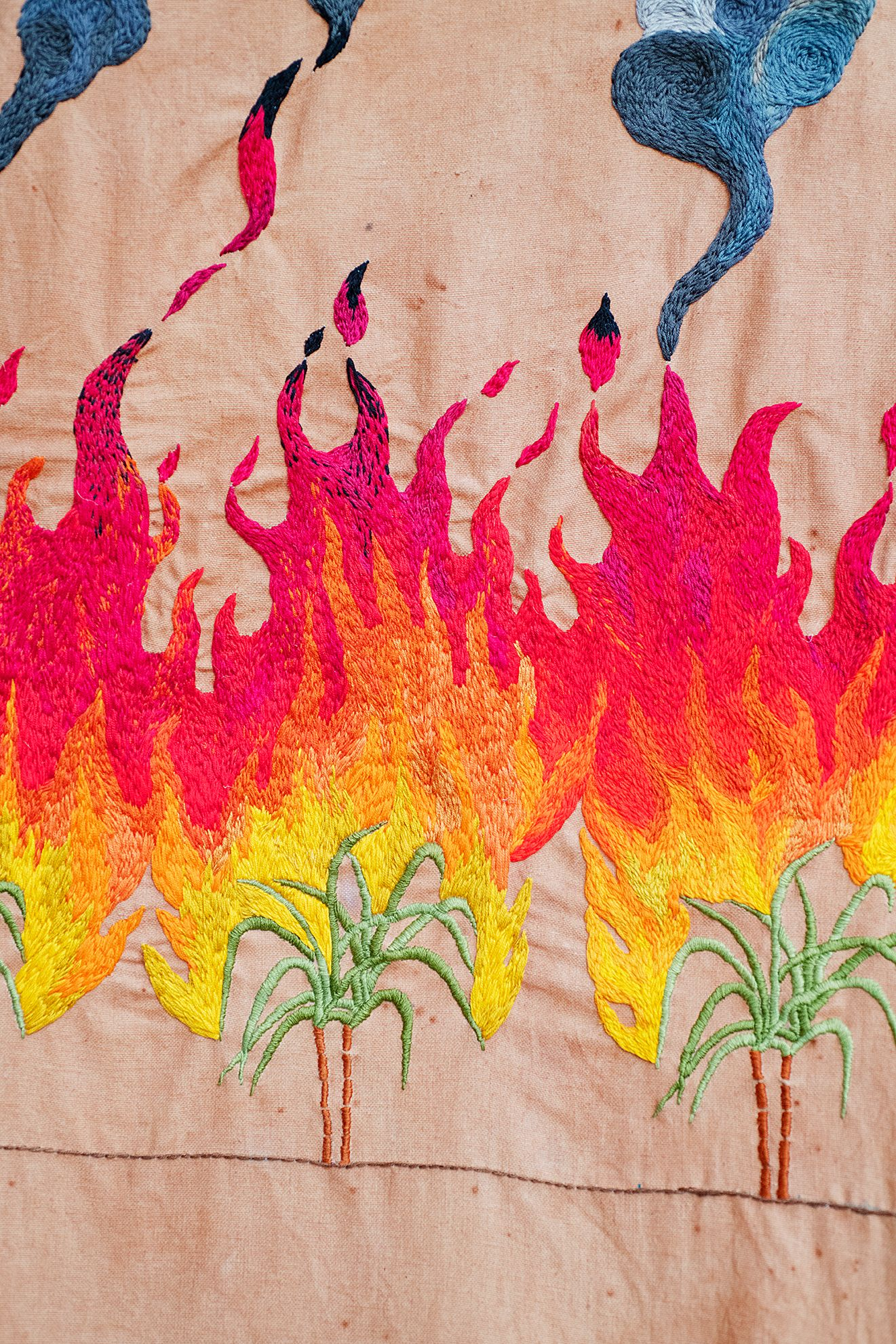Quishile Charan, Burning Ganna Khet, 2021, cotton, embroidery thread, hessian sacks, natural dye: avocados, 153cm by 152cm. Close up of embroidery. Image taken by: Raymond Sagapolutele.