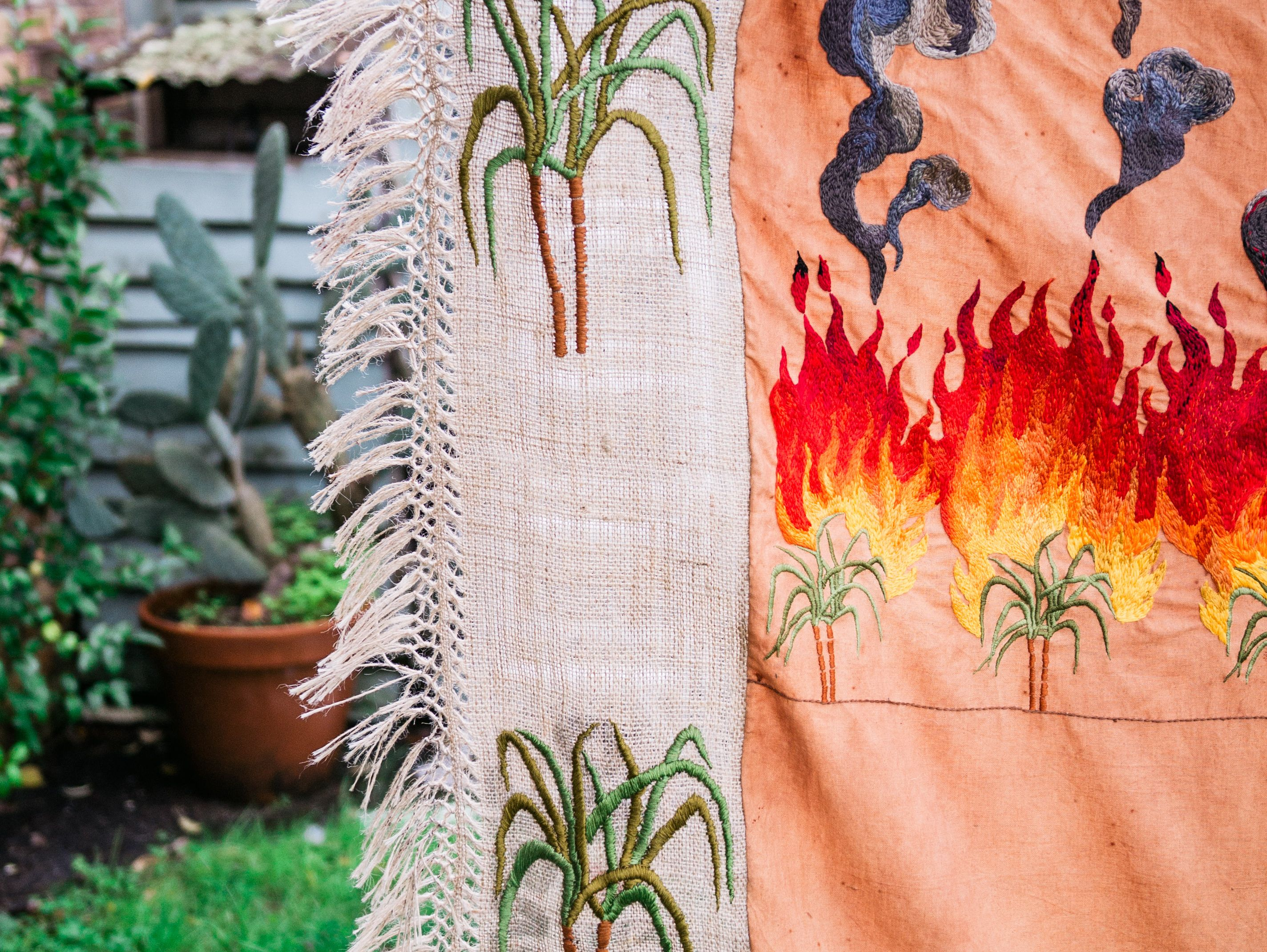 Quishile Charan, Burning Ganna Khet (Burning Sugarcane Farm), 2021, 153cm by 152cm. Technique: hand dyed textile, embroidery thread, cotton, hessian sacks. Textile is naturally dyed with avocado seeds. Image by Matavai Taulangau.